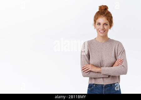 Confident, good-looking redhead caucasian female in sweater, curly hair combed in bun, cross arms over chest self-assured, smiling assertive and - Stock Photo
