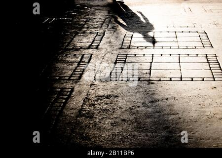 Blurry shadow silhouette on city sidewalk of mysterious man walking alone - Stock Photo