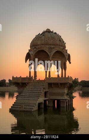 Sunrise and temple Gadi Sagar, Gadisar Lake, Jaisalmer, Rajasthan, India - Stock Photo