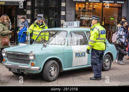 London, January 26, 2020. Policemans standing by his police car.Police sign on an Austin patrol car.AUSTIN1300 Police Panda car - Stock Photo
