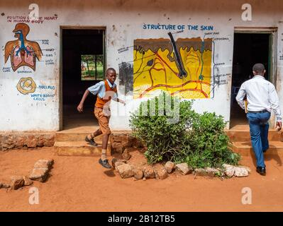 A pupil leaving and a teacher entering classrooms at a rural junior school near Voi in Southern Kenya