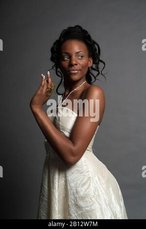 Young dark-skinned woman wearing an ivory-colored dress - Stock Photo