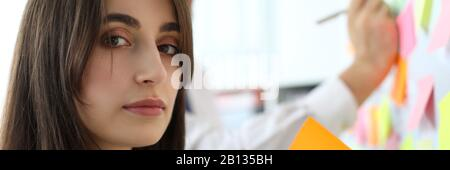 Pretty female office worker holding sticky paper looking in camera