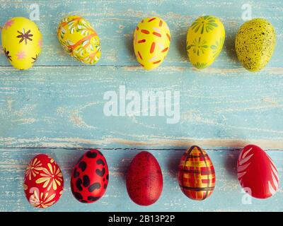 Easter eggs are arranged in two rows between yellow and red on a pastel blue wood floor. Vintage style coloring - Stock Photo