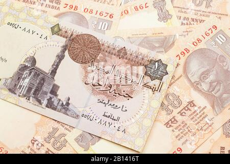 A close up image of an Egyptian one pound bank note with Indian ten rupee bank notes in macro - Stock Photo
