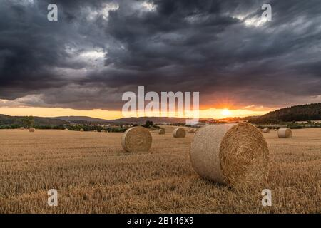 Storm over a stubble field at sunset, Thuringia, Germany - Stock Photo