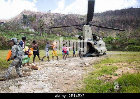 U.S. Army Sgt. Delton Reynolds, left, a flight engineer with Joint Task Force - Leeward Islands, joins a chain with local residents and members of the Jamaican Defence Force to unload relief supplies from a CH-47 Chinook helicopter at Wotten Waven, Dominica, Oct. 3, 2017. The aircraft delivered rice and kitchen sets from the U.S. Agency for International Development to the community. At the request of USAID, JTF-LI has deployed aircraft and service members to assist in delivering relief supplies to Dominica in the aftermath of Hurricane Maria. The task force is a U.S. military unit composed of - Stock Photo