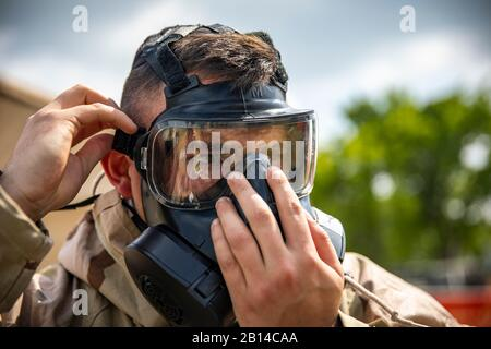 A U.S. Marine with Marine Aircraft Group 41, 4th Marine Aircraft Wing, puts on a M-50 joint service general purpose mask during a chemical, biological, radiological and nuclear (CBRN) individual survival skills course in support of Sentinel Edge 19 (SE19) at Canadian Forces Base Cold Lake, Canada, June 14, 2019. CBRN training test Marines abilities to respond in the event of chemical, biological, radiological or nuclear contamination. Training exercises such as SE19 ensure Reserve Marines are proficient and capable of successful integration with active-duty Marines, making Marine Forces Reserv Stock Photo