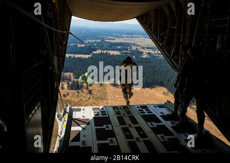 A U.S.  Soldier with the 1st Battalion, 1st Special Forces Group (SFG) jumps from a KC-130J Hercules with Marine Aerial Refueler Transport Squadron (VMGR) 152, during air delivery training for a static line jumpmaster course at Joint Base Lewis-McChord, Washington, Aug. 22, 2017. The air delivery was part of unit-level training Evergreen. Air delivery maximizes the number of personnel and equipment rapidly delivered to a forward location, with little or no ground support in the objective area. Evergreen will serve as VMGR-152's 2017 Marine Corps Combat Readiness Evaluation through tri-lateral - Stock Photo