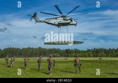 U.S. Marines with Landing Support Company, 2nd Transportation Support Battalion, Combat Logistics Regiment 2, and Marine Heavy Helicopter Squadron 464, Marine Aircraft Group 29, 2nd Marine Aircraft Wing, lift a medium girder bridge at Camp Lejeune, North Carolina, May 2, 2019. 2nd TSB and HMH-464 worked together in order to lift and move a medium girder bridge with CH-53E Super Stallion to improve operational capabilities. (U.S. Marine Corps photo by Cpl. Damion Hatch Jr.) - Stock Photo