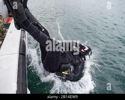 U.S. Navy Builder 2nd Class Aaron Brown, assigned to Underwater Construction Team (UCT) 2, enters the water for a mooring buoy inspection at Commander, Fleet Activities Sasebo, Japan, Jan. 11, 2018. UCT-2 provides construction, inspection, maintenance, and repair of underwater and waterfront facilities in support of the Pacific Fleet. (U.S. Navy Combat Camera photo by Mass Communications Specialist 1st Class Arthurgwain L. Marquez) - Stock Photo
