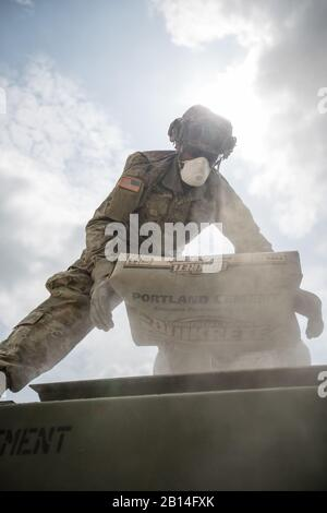 U.S. Army Reserve Spc. Marcelles Riggs, 943rd Engineer Detachment, 416th Engineer Command, loads a bag of concrete into an M5-Concrete Mobile Mixer during Combat Support Training Exercise (CSTX) 86-18-02 at Fort McCoy, Wis., August 16, 2018.  This is the second CSTX of the summer for the 86th Training Division. The CSTX exercise is a large-scale training event where units experience tactical training scenarios specifically designed to replicate real-world missions. (U.S. Army Reserve Photo by Spc. John Russell) - Stock Photo