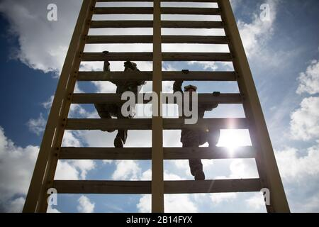 Two U.S. Marines assigned to Special Purpose Marine Air Ground Task Force-Crisis Response-Africa climb a 30-foot ladder during a fast rope exercise at Naval Station Rota, Spain, March 24, 2017. Infantry Marines maintain their fast-roping qualifications in order to remain proficient and prepare to fast rope from an aircraft as a tactical insertion method. (U.S. Marine Corps photo by Sgt. Jessika Braden) - Stock Photo