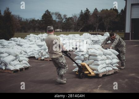 More than 30 U.S. Airmen assigned to the 107th Attack Wing, Niagara Falls Air Reserve Station, New York Air National Guard, were activated by Gov. Andrew Cuomo to respond to rising water levels in Lake Ontario which has led to flooding and a state of emergency, Olcott, N.Y., May 12, 2017. The Airmen filled more than 47,000 sandbags to be deployed throughout the Lake Ontario area to hold back flooding since being activated  May 9. (U.S. Air National Guard photo by Staff Sgt. Ryan Campbell) - Stock Photo