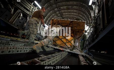 U.S. Air Force Staff Sgt. Terrico Cadogan, assigned to the 42nd Aerial Port Squadron, pushes cargo into a C-17 Globemaster III Sept. 23, 2017, at Dobbins Air Reserve Base, Ga. Airmen assigned to Joint Base Charleston provided relief efforts to those recently affected by Hurricanes Irma and Maria. Support items they brought included pallets of meals ready to eat, cases of water and a stand-up air traffic mobile control tower to support the relief effort operations of St. Thomas Cyril E. King Airport. (U.S. Air Force photo by Senior Airman Clayton Cupit) - Stock Photo