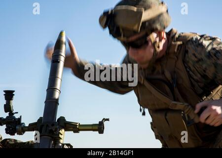 U.S. Marine Corps Lance Cpl. Dylan Sheperd, an assistant gunner, loads a round into an M224 60mm mortar system during a live-fire mortar range at Camp Lejeune, N.C., Dec. 19, 2017. The unit used the hand-held, direct lay and direct alignment methods to engage targets 1,500 meters away. This provided Marines with India Company, 3rd Battalion, 6th Marine Regiment, 2nd Marine Division the opportunity to increase their proficiency and familiarization with the weapon system. (U.S. Marine Corps photo by Cpl. Aaron Henson) - Stock Photo