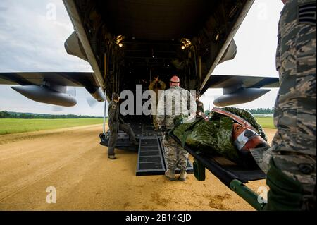 U.S. Airmen transfer patients from an ambulance bus to a C-130 Hercules as part of a simulated aeromedical evacuation at Young Air Assault Strip, Fort McCoy, Wis., Aug. 18, 2017, during exercise Patriot Warrior. More than 600 Reserve Citizen Airmen and over 10,000 soldiers, sailors, Marines and international partners converged on the state of Wisconsin to support a range of interlinked exercises including Patriot Warrior, Global Medic, CSTX, Diamond Saber, and Mortuary Affairs Exercise (MAX).  Patriot Warrior is Air Force Reserve Command's premier exercise, providing an opportunity for Reserve - Stock Photo