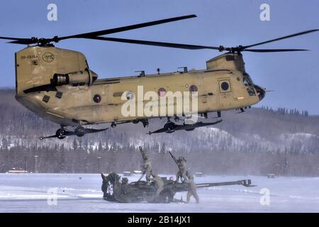 U.S. Soldiers assigned to Battery C, 2nd Battalion, 8th Field Artillery Regiment battle stiff winds, sub-zero temperatures and blowing snow as they prepare to hook up their 155mm howitzer to a CH-47 Chinook helicopter for the flight to the Yukon Training Area, Alaska, March 7, 2018. The exercise, Automatic Big Rig, was part of the first gun raid in three years for the 2nd Battalion, 8th Field Artillery Regiment, and was carried out in conjunction with helicopter support from the 1st Battalion, 52nd Aviation Regiment. The field artillery regiment is part of the 1st Stryker Brigade Combat Team, - Stock Photo