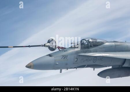 A Royal Canadian Air Force CF-18 Hornet refuels from a CC-150T Polaris refueler during a sortie for Red Flag-Alaska 19-3 over the Joint Pacific Alaska Range Complex, Alaska, August 15, 2019. RF 19-3 includes international participation from the Royal Air Force, the Royal Canadian Air Force, and the Royal Australian Air Force. RF-A is a Pacific Air Forces-directed field training exercise for U.S. and international forces flown under simulated air combat conditions. It is conducted on the JPARC with air operations flown out of Eielson Air Force Base and Joint Base Elmendorf-Richardson. (U.S. Air - Stock Photo