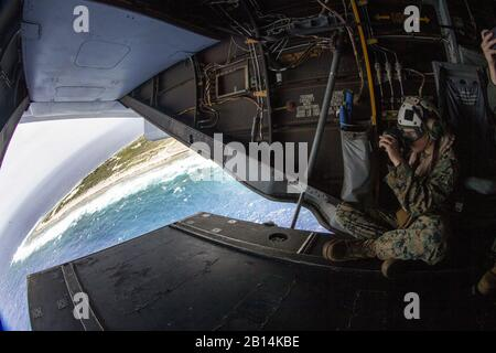 U.S. Marine Corps Lance Cpl. Zachary Brunk, a landing support specialist with Combat Logistics Battalion 11, 11th Marine Expeditionary Unit (MEU), captures images while riding in an MV-22 Osprey during a fly-over of Wake Island in the Pacific Ocean, May 23, 2019. The Marines and Sailors of the 11th MEU are deployed to the U.S. 7th Fleet area of operations to support regional stability, reassure partners and allies, and maintain a presence postured to respond to any crisis ranging from humanitarian assistance to contingency operations (U.S. Marine Corps photo by Lance Cpl. Dalton S. Swanbeck) Stock Photo
