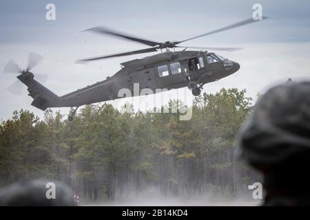 U.S. Army National Guard Soldiers from New Jersey's 250th Brigade Support Battalion look on as a UH-60M Black Hawk helicopter from the 1st Assault Helicopter Battalion, 150th Aviation Regiment arrives at Landing Zone 14 for sling load training on Joint Base McGuire-Dix-Lakehurst, N.J., May 4, 2019. (U.S. Air National Guard photo by Master Sgt. Matt Hecht) - Stock Photo