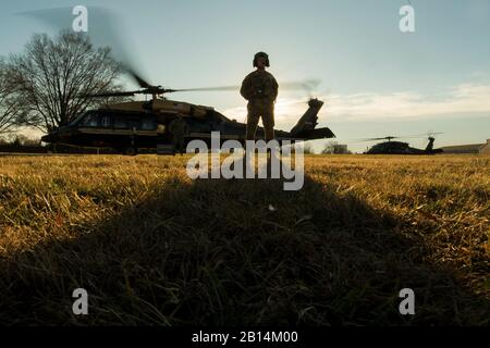 A U.S. Army aircrewman awaits the arrival of Marine Corps Gen. Joe Dunford, the chairman of the Joint Chiefs of Staff, outside a VH-60N White Hawk helicopter before departing Joint Base Myer-Henderson Hall, Virginia, Dec. 7, 2017. Dunford visited the Army War College at Carlisle Barracks, Pa., to discuss Marine Corps operations with students and staff. (DoD photo by U.S. Navy Petty Officer 1st Class Dominique A. Pineiro) - Stock Photo
