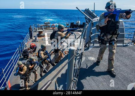 U.S. Sailors board the Ticonderoga-class guided-missile cruiser USS Lake Champlain (CG 57) as part of a visit, board, search and seizure drill in the Pacific Ocean Feb. 17, 2018. Lake Champlain is currently operating in the Pacific as part of the Carl Vinson Strike Group. (U.S. Navy photo by Mass Communication Specialist 1st Class Nathan Carpenter) - Stock Photo