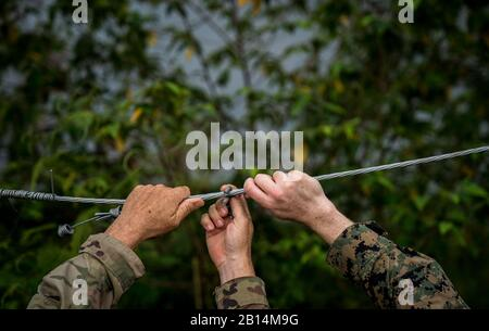 U.S. Army Maj. Robert Vandertuin, left, and U.S. Marine Maj. Jeremy Carroll fix a wire on a fence that helps mitigate elephant stampedes of up to 40 elephants in the area in Chachoengsao, Kingdom of Thailand, Jan. 31, 2018. Vandertuin is the head of a Combined Joint Civil Military Operations Task Force.  Exercise Cobra Gold 2018 is an annual exercise conducted in the Kingdom of Thailand and runs from Feb. 13-23 with up to nine nations participating. (U.S. Marine Corps photo by Sgt. Matthew J. Bragg) - Stock Photo
