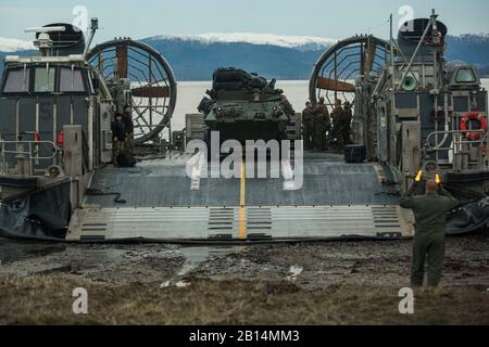 U.S. Marines and Sailors offload a light armored vehicle from a landing craft, air cushion on Alvund Beach, Norway, during an amphibious landing in support of Trident Juncture 2018, Oct. 30, 2018. Trident Juncture provides a unique environment for the Marines and Sailors to rehearse their amphibious capabilities. The LCACs originated from USS New York (LPD 21) and showcased the ability of the Iwo Jima Amphibious Ready Group and the 24th Marine Expeditionary Unit to rapidly project combat power ashore. The vehicles and Marines are with 2nd Light Armored Reconnaissance Battalion, 24th MEU. (U.S. - Stock Photo