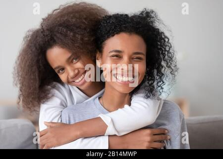 Happy african family mother and teen girl embracing mom, portrait - Stock Photo