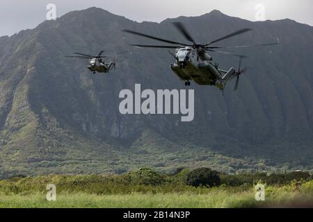 U.S. Marine Corps CH-53E Super Stallions assigned to Marine Heavy Helicopter Squadron (HMH) 463 prepare to land and drop off U.S. Marines with India Company, 3rd Battalion, 3rd Marine Regiment, during a helicopter insertion exercise at Marine Corps Training Area Bellows (MCTAB), Hawaii, Sept. 18, 2018. The company inserted into MCTAB with CH-53E Super Stallions to establish a secure landing zone, patrol over roads and through jungle terrain, and to clear simulated villages of hostiles. (U.S. Marine Corps photo by Sgt. Jesus Sepulveda Torres) - Stock Photo