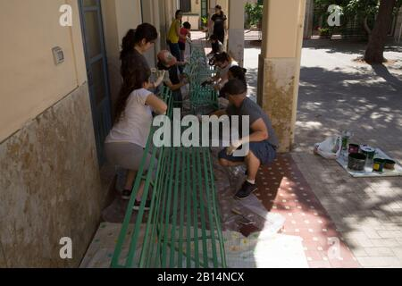 U.S. Marines and Sailors with Special Purpose Marine Air-Ground Task Force-Crisis Response-Africa 19.2, Marine Forces Europe and Africa, and local children paint benches at the Pio IX Orphanage in Catania, Sicily, Italy, June 20, 2019. Marines and Sailors with SPMAGTF-CR-AF 19.2 volunteered to assist an orphanage in the city of Catania with renovations by painting, moving, and cleaning their building. (U.S. Marine Corps photo by Staff Sgt. Mark E. Morrow Jr.) - Stock Photo