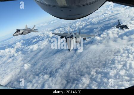 A Royal Air Force F-35 Lightning II aircraft, left, U.S. Air Force F-15E Strike Eagle, center, and French air force Dassault Rafale fly behind a U.S. Air Force KC-135 Stratotanker assigned to the 100th Air Refueling Wing during Exercise Point Blank over the English Channel, Nov. 27, 2018. Training with NATO allies like the U.K. and France improves interoperability and demonstrates the United States' commitment to regional security. Exercise Point Blank also represents an opportunity to enhance interoperability and integration between allied fourth and fifth-generation fighter aircraft. (U.S. A - Stock Photo