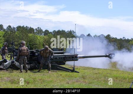U.S. Marines conduct a live-fire shoot with an M777 howitzer during a unit reunion at Camp Lejeune, N.C., April 25, 2017. The reunion gave retirees and their families an opportunity to witness new weapons systems and interact with the new generation of field artillery Marines. The Marines are with 1st Battalion, 10th Marine Regiment, 2nd Marine Division. (U.S. Marine Corps photo by Sgt. Clemente C. Garcia) - Stock Photo