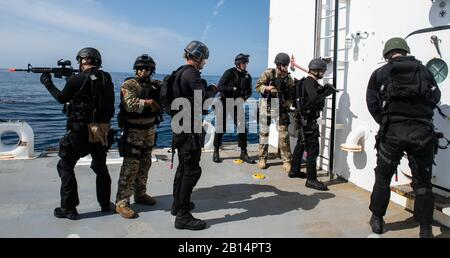 U.S. Sailors assigned to the Harpers Ferry-class amphibious dock landing ship USS Harpers Ferry (LSD 49) visit, board, search, and seizure team boards and prepare to search motor vessel MV ATLS-9701 during a VBSS training exercise in the Pacific Ocean, March 24, 2019. Harpers Ferry was underway conducting routine operations as a part of USS Boxer Amphibious Ready Group (ARG) in the eastern Pacific Ocean. (U.S. Navy photo by Mass Communication Specialist 3rd Class Danielle A. Baker) - Stock Photo