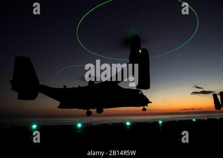 A U.S. Marine Corps MV-22B Osprey tiltrotor aircraft, assigned to Marine Medium Tiltrotor Squadron (VMM) 262 (Reinforced), with the embarked 31st Marine Expeditionary Unit (MEU), takes off from the flight deck of the amphibious assault ship USS Wasp (LHD 1) during night flight operations in the Philippine Sea Jan. 28, 2019. The Wasp, flagship of the Wasp Amphibious Ready Group, with embarked 31st MEU, is operating in the Indo-Pacific region to enhance interoperability with partners and serve as a ready-response force for any type of contingency. (U.S. Navy photo by Mass Communication Specialis - Stock Photo