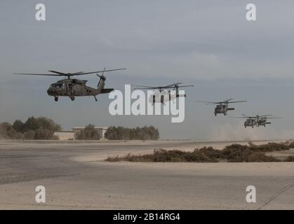 U.S. Army UH-60 Black Hawk helicopters take off in unison carrying distinguished visitors after Army Day demonstrations, Feb. 9, 2018, Kuwait Naval Base, Kuwait. Army Day was the opening event for U.S. Central Command's Component Commanders Conference that allowed U.S. Army Central to showcase the Army's capabilities at the theater level. (U.S. Army photo by Sgt. 1st Class Ty McNeeley) - Stock Photo