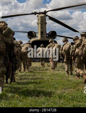 Paratroopers from 1st Battalion, 503rd Parachute Infantry Regiment (PIR), 173rd Infantry Brigade Combat Team (Airborne) mount a CH-47 Chinook helicopter during exercise Immediate Response 19 at Udbina Airbase, Croatia, May 17, 2019. IR 19 is a multi-domain, realistic and challenging exercise training the U.S. and its allies and partners to fight together and improve military mobility. (U.S. Army photo by Pvt. Laurie Ellen Schubert) - Stock Photo