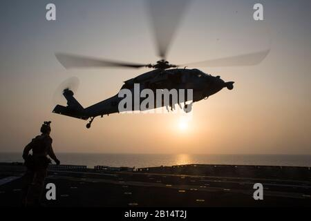 A U.S. Navy SH-60 Sea Hawk helicopter carrying Maritime Raid Force (MRF) Marines with the 24th Marine Expeditionary Unit hovers over the amphibious assault ship USS Bataan (LHD 5) during a fast-rope exercise in the U.S. 5th Fleet area of responsibility March 29, 2017. The MRF trains regularly to stay mission capable while deployed with the 24th MEU. The 24th MEU was deployed with the Bataan Amphibious Ready Group in support of maritime security operations and theater security cooperation efforts in the 5th Fleet area of operation. (U.S. Marine Corps photo by Cpl. Brianna Gaudi) - Stock Photo