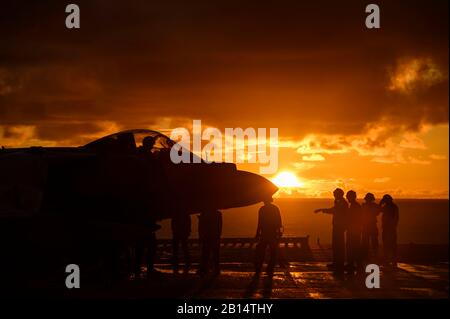 U.S. Marines aboard amphibious assault ship USS Boxer (LHD 4) conduct post-flight checks on an AV-8B Harrier II attached to Marine Medium Tiltrotor Squadron (VMM) 163 during flight operations on the flight deck in the Pacific Ocean, May 26, 2019. The Boxer Amphibious Ready Group (ARG) and 11th Marine Expeditionary Unit (MEU) are deployed to the U.S. 7th Fleet area of operations to support regional stability, reassure partners and allies, and maintain a presence to respond to any crisis ranging from humanitarian assistance to contingency operations. (U.S. Navy photo by Mass Communication Specia - Stock Photo