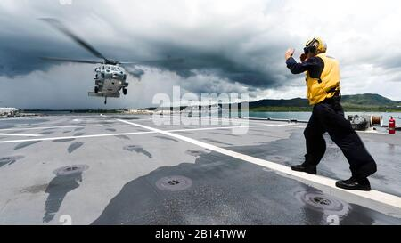 Boatswain's Mate 2nd Class Paul Coombs directs an MH-60S Seahawk helicopter to the flight deck aboard the littoral combat ship USS Coronado (LCS 4) while the ship is moored at Naval Base Guam. Coronado is on a rotational deployment in U.S. 7th Fleet area of responsibility, patrolling the region's littorals and working hull-to-hull with partner navies to provide 7th Fleet with the flexible capabilities it needs now and in the future. (U.S. Navy photo by Mass Communication Specialist 2nd Class Kaleb R. Staples/Released) - Stock Photo