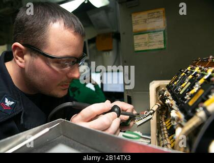 U.S. Navy Aviation Electronics Technician 2nd Class Randall Hutton solders a connecting wire in the generator shop aboard the Nimitz-class aircraft carrier USS Harry S. Truman (CVN 75) in the Norwegian Sea Oct. 26, 2018. Currently operating in the U.S. Sixth Fleet area of operations, the Harry S. Truman will continue to foster cooperation with regional allies and partners, strengthen regional stability, and remain vigilant, agile and dynamic. (U.S. Navy photo by Mass Communication Specialist 3rd Class Sean Elliott) - Stock Photo