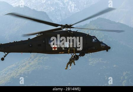 U.S. Army Sgt. 1st Class Jessie Turner, a flight paramedic with the 2nd General Support Aviation Battalion, 4th Aviation Regiment, 4th Combat Aviation Brigade, 4th Infantry Division, is hoisted up into a HH-60 Black Hawk helicopter at Litochoro, Greece, Jan. 23, 2019. Regionally allocated forces conduct training regularly to maintain readiness and lethality, and participate in future training exercises with partners and allies. (U.S. Army photo by Staff Sgt. Kris Bonet) - Stock Photo