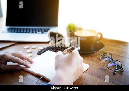 Male manager putting his ideas and writing business plan at workplace,man holding pen and making note in notebook , on the table in office,vintage col - Stock Photo