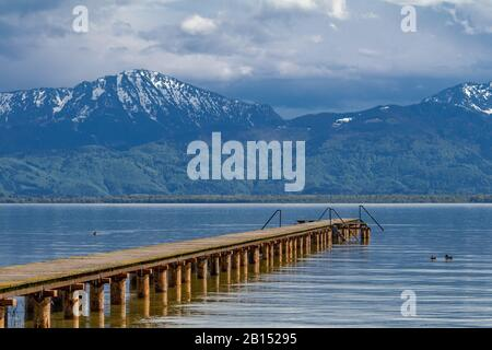 lake Chiemsee with bathing jetty and snow covered Alps in spring , Germany, Bavaria, Lake Chiemsee - Stock Photo