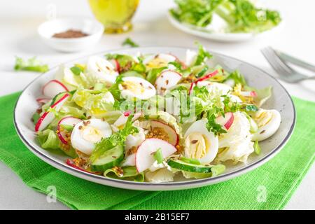 Fresh vegetable salad with cucumber, radish, lettuce and boiled eggs. Helathy food. Top view. Flat lay - Stock Photo