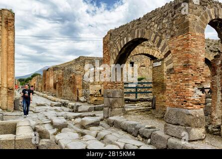 POMPEII, ITALY - MAY 13, 2014: Tourist walking in the street among the ruins. Pompeii is an ancient Roman city died from the eruption of Mount Vesuviu - Stock Photo