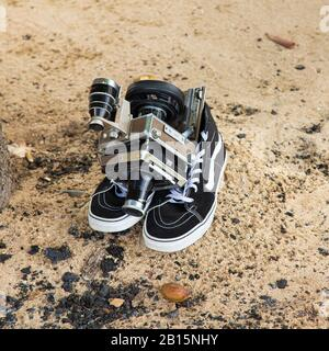 Linhof Universal Sucher Technika film/video camera on a pair of modern high-top sneakers on a sandy beach in front of charcoal left from a barbecue - Stock Photo