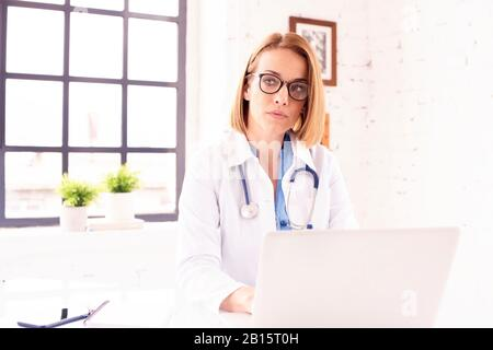 Shot of middle aged female doctor sitting behind her laptop and working.