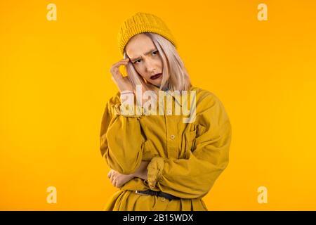 Young upset woman with white hair having headache, studio portrait. - Stock Photo